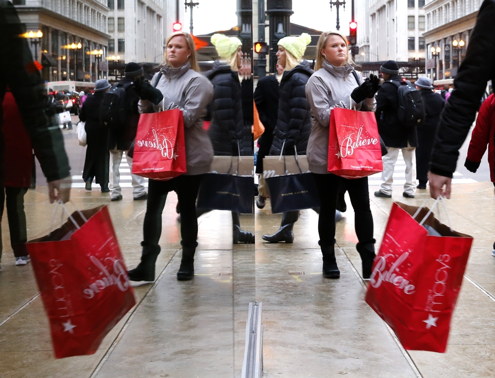 Shoppers are reflected in a store's window as they walk through Chicago's Loop on Christmas Eve. U.S. businesses, consumers and investors made steady gains in 2014.