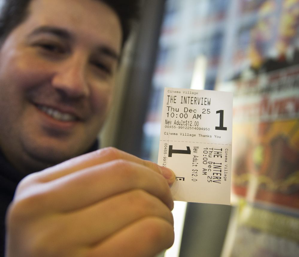 """Derek Karpel holds his ticket to a screening of """"The Interview"""" at Cinema Village movie theater in New York on Thursday. The film raked in just over $1 million in ticket sales."""