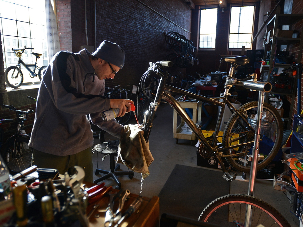 Karl Borne works on a bicycle at the Merrimack Valley YMCA's BiciCocina, or Bike Kitchen, in Lawrence, Mass.
