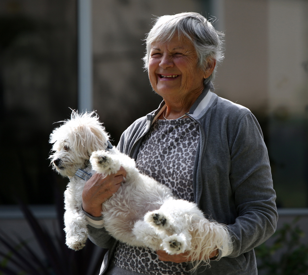 Jovanka Radivojevic, 78, a retired physician, holds her 5-year-old dog Sugar, who survived a recent coyote attack in front of Radivojevic's home in Seal Beach, Calif.