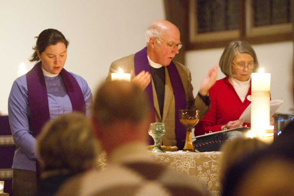 Deacon Kelly Moughty, the Rev. Timothy Boggs and Karen Rea, chalice bearer, stand at the altar during communion at St. Alban's Episcopal Church in Cape Elizabeth during a Celtic Eventide service on Dec. 7.
