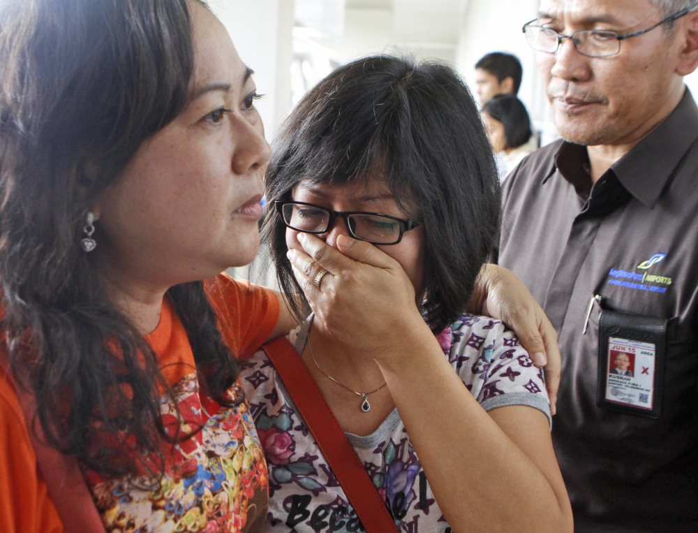 A relative of AirAsia flight 8501 passengers weeps as she waits for the latest news on the missing jetliner at Juanda International Airport in Surabaya, East Java, Indonesia, on Sunday.
