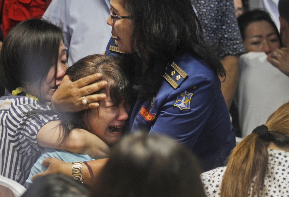 Relatives of passengers of AirAsia Flight 8501 react to news on television Tuesday about the discovery of bodies in the waters near where the jetliner disappeared. The Associated Press