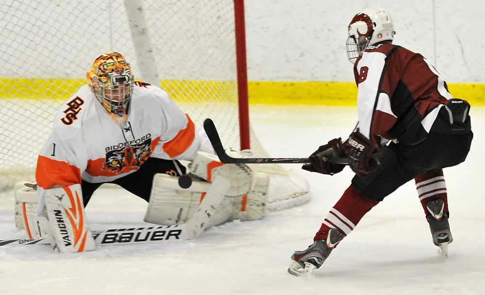 Biddeford goalie Brandon Daigle saves a breakaway by Bangor's Nick Graham in their game Tuesday at Biddeford Ice Arena. Bangor dominated from the start, outshooting the Tigers 37-13, 26-5 over the final two periods.