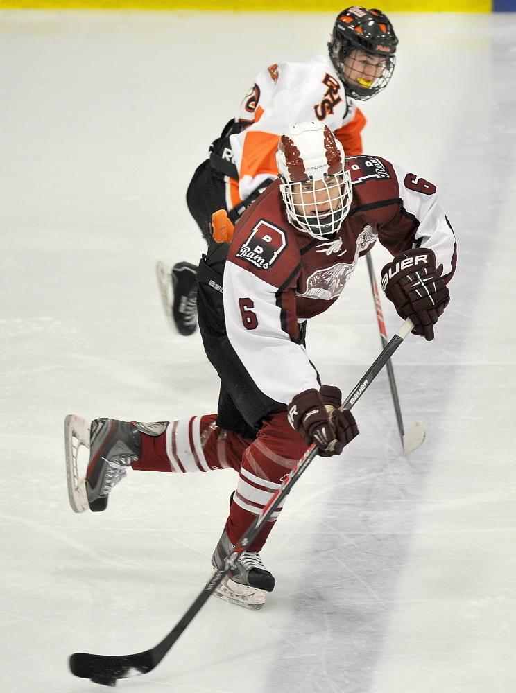 Bangor's Trevor DeLaite looks for an open man while being chased by a Biddeford opponent .