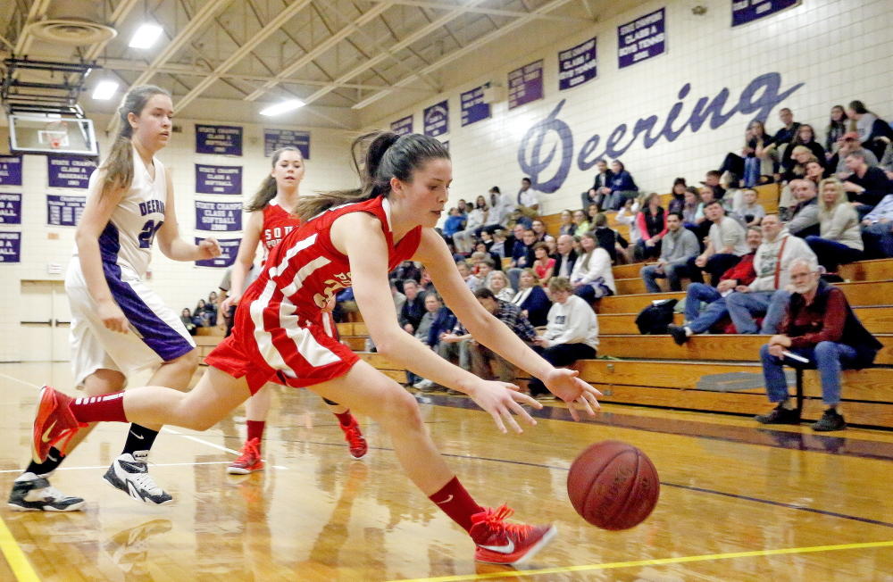 South Portland's Maddie Hasson tries to rescue the ball before it goes out of bounds as Deering's Katie Howard, background, looks on,  during a girls basketball game at Deering on Tuesday.