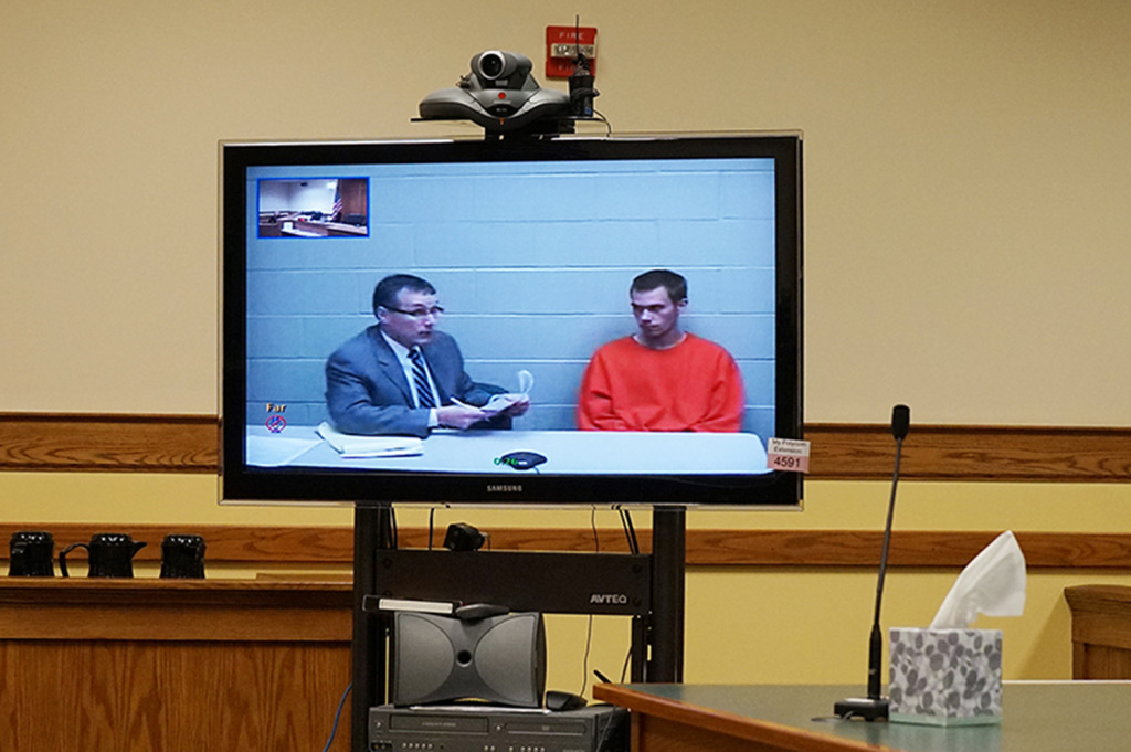 Shane Jones, right, appears by video link in Springvale District Court, seated beside attorney Scott Houde at the York County Jail, to face charges related to his mother's death.