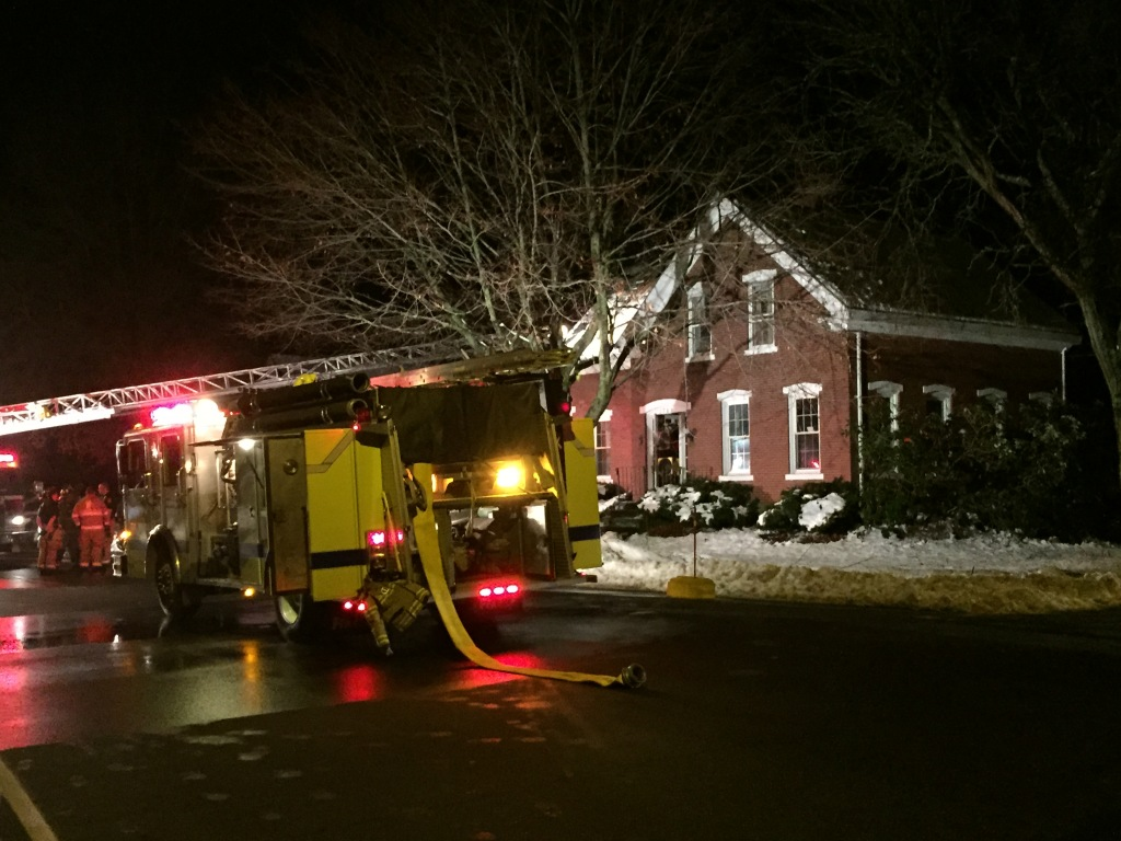 A firetruck sits outside the 251-year-old home damaged by fire late Sunday on East Bridge Street in Westbrook. The fire apparently started around a wood stove's exhaust piping. Kevin Miller/Staff Writer