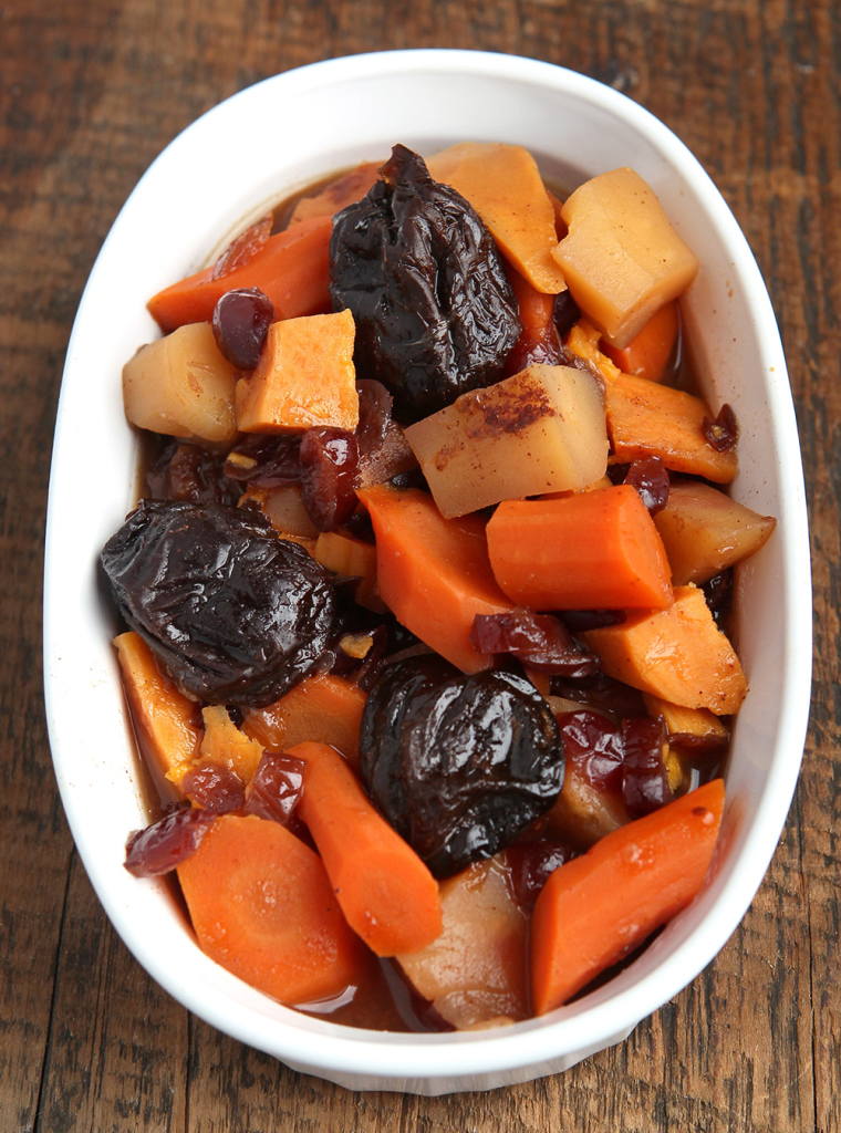 Tzimmes prepared with carrots, sweet potatoes, parsnips, prunes, cranberries and cinnamon.
