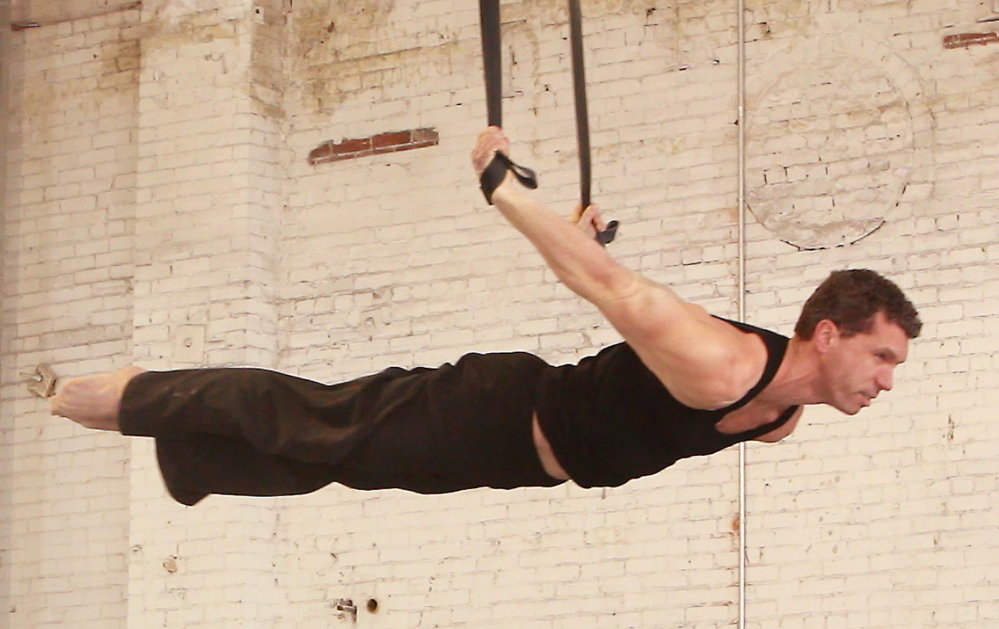 Joshua Oliver, technical director of the Circus Conservatory of America, performs on a pair of black straps in this file photo. The group's new training center opened in January as the first tenant on Thompson's Point, where a $100 million development is planned. The school announced Wednesday it has suspended operations.