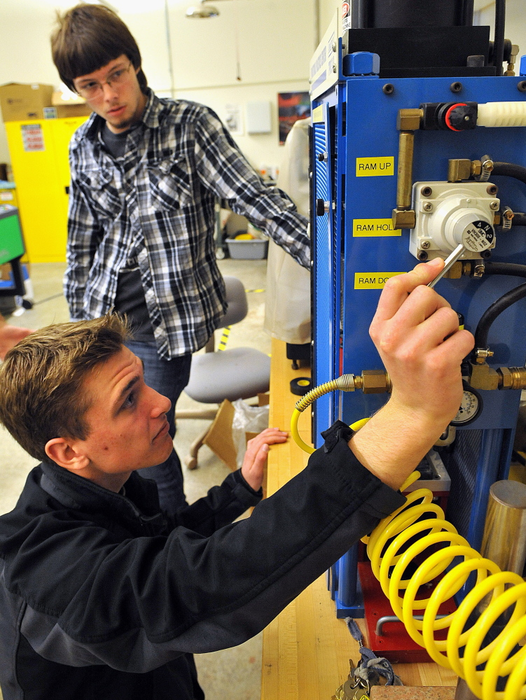 Butler County Community College sophomores Zach Staebler, front, and Mike Paul work an injection molding machine in the school's manufacturing lab.