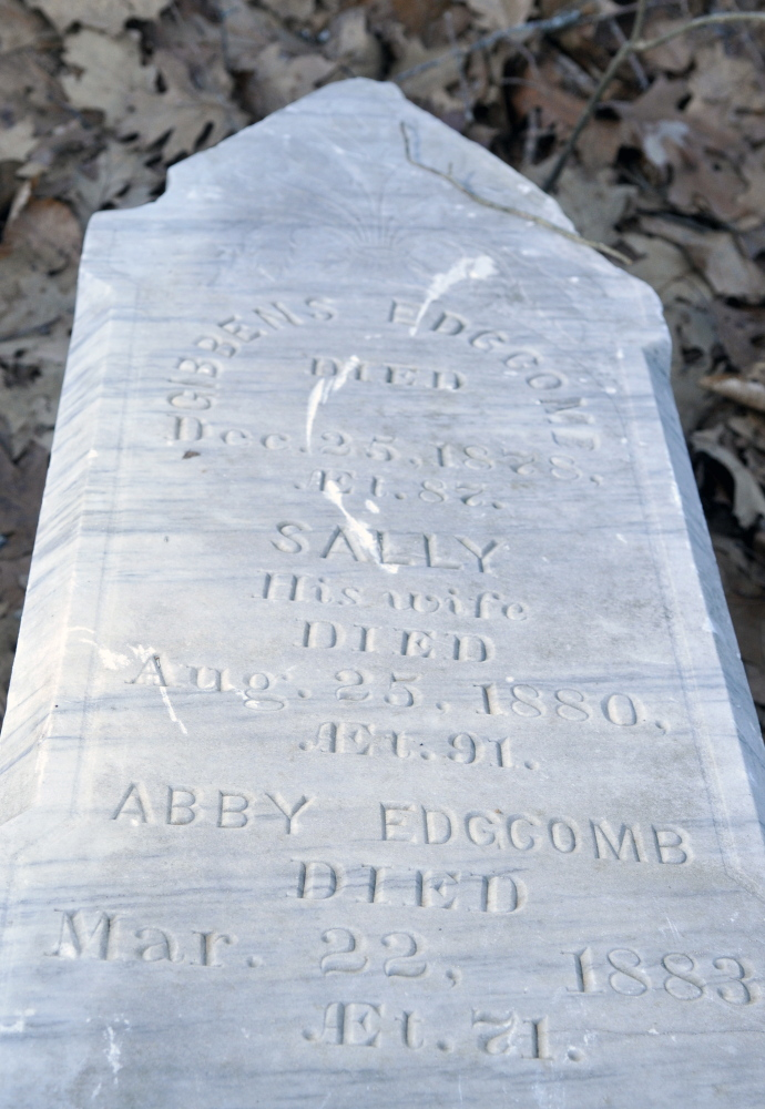 An obelisk grave marker with names on all four sides has toppled to the bottom of the hill at Edgecomb cemetery in Gardiner.