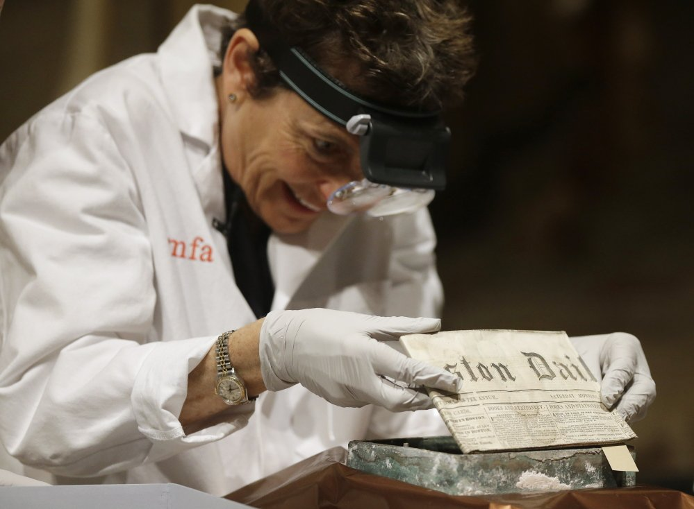 Museum of Fine Arts Boston Head of Objects Conservation Pam Hatchfield removes a folded 19th century newspaper from the time capsule.