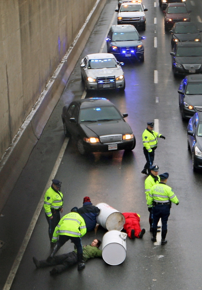 Protesters block the morning commute Thursday in Milton, Mass. Activists chained themselves to concrete-filled barrels and blocked a busy Boston area highway in two places.