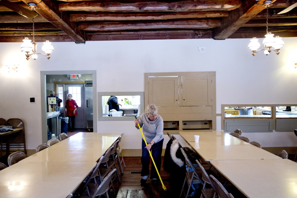 Volunteer Barbara Reaves of Freeport sweeps the hall of the Pownal Center Congregational Church after she helped serve a meal to the elderly Thursday. The 200-year-old church relies on tips and tries to serve the meals as often as possible. Under the governor's tax plan, the town of 1,500 would probably lose revenue and could be forced to raise property taxes.