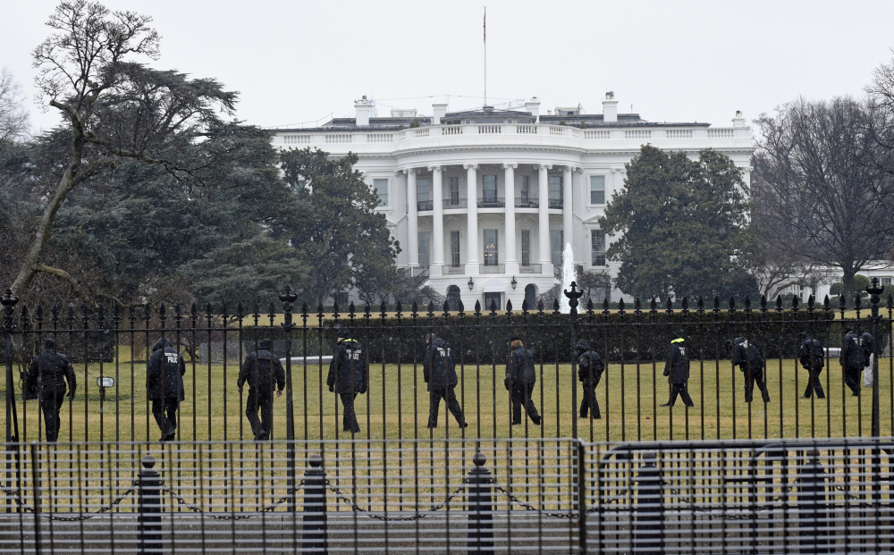 Secret Service officers search the south grounds of the White House in Washington on Jan. 26 after a drone was found during the middle of the night. President Barack Obama and the first lady were in India at the time. The Associated Press