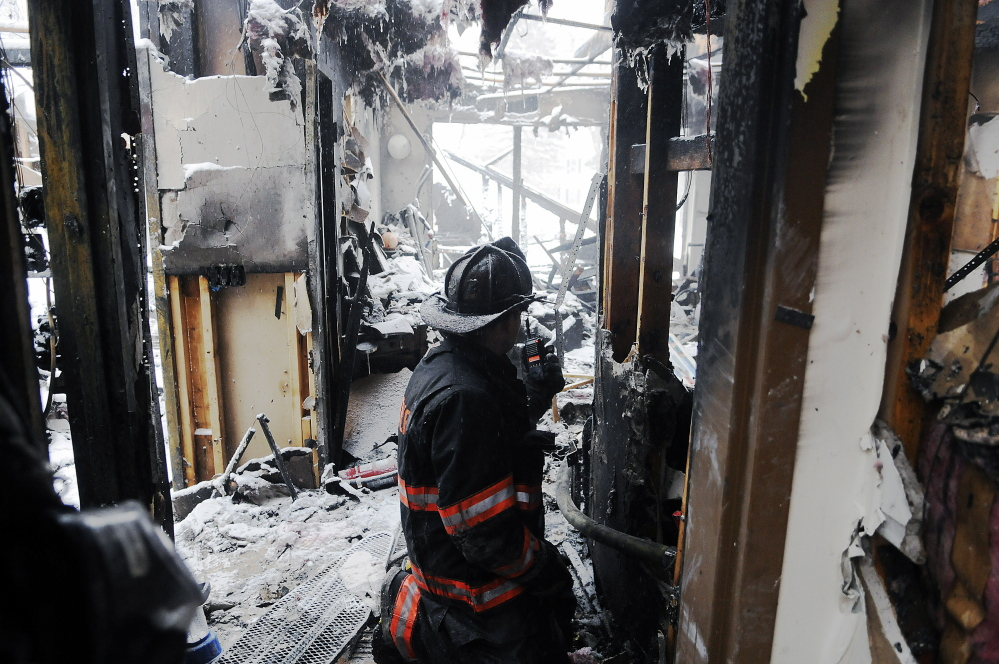 A firefighter crawls into Highland Terrace in Gardiner on Thursday, a day after fire destroyed about half of the senior housing complex. Gardiner Fire Chief Al Nelson said Sunday the cause of the fire is determined to be accidentla, and likely an electrical issue.