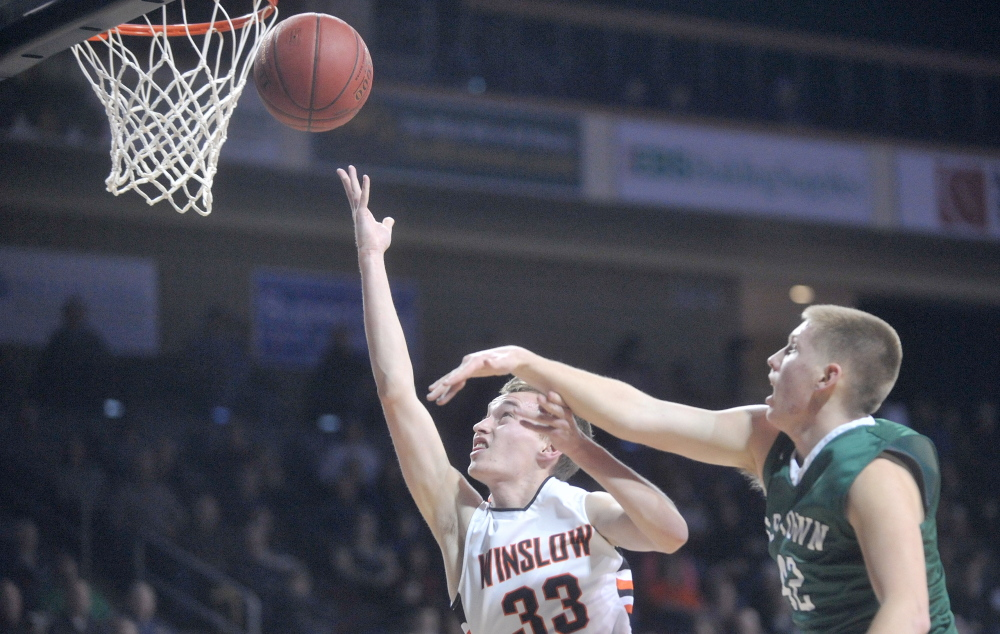 Winslow High School's Justin Burgher, left, drives past old Town High School's Adam Richardson in the first half of an Eastern B semifinal at the Cross Insurance Center in Bangor on Wednesday. Winslow prevailed 48-44.