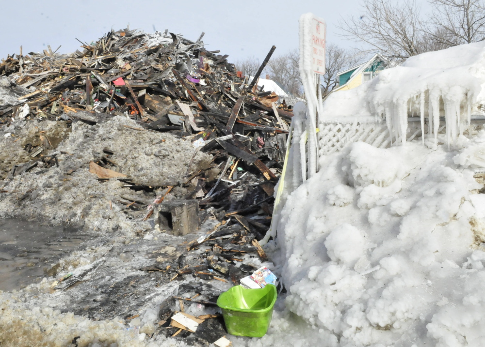 An apartment building on Paris Street in Waterville, shown Tuesday, has been reduced to ice-covered rubble since a fire destroyed it Monday.