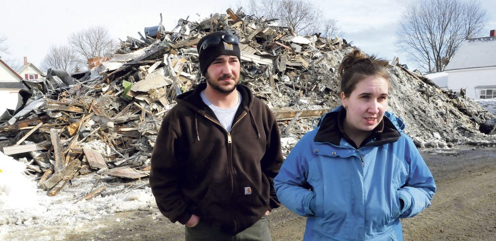 Chad Dambois and Megan Hale speak on Tuesday in front of a pile of rubble, all that remains of the apartment building where they lived until a fire destroyed it Monday. Hale said she lost everything, including irreplaceable personal belongings.