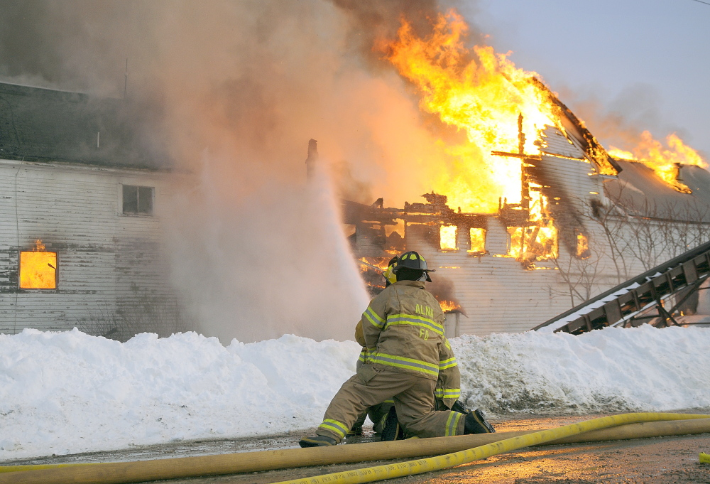 Firefighters attempt to prevent flames from the barn from spreading into the house on Tuesday at the Fenderson farm in Whitefield. The flames destroyed the dairy farm during the afternoon blaze.