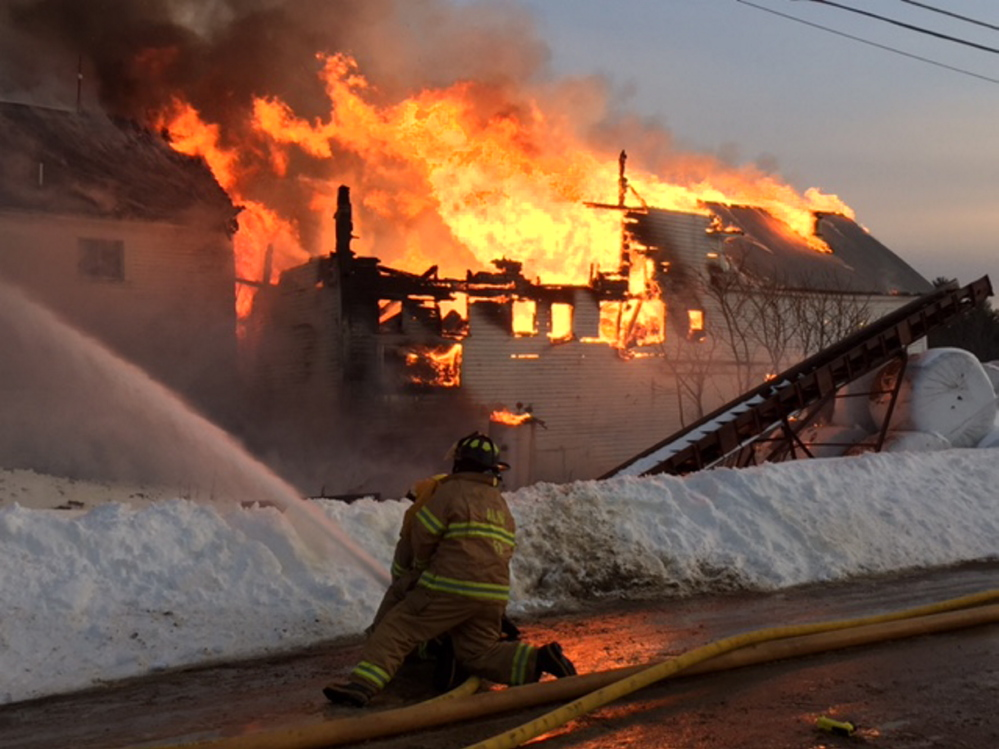 A firefighter sprays water on a fire on Hilton Road in Whitefield, where crews from several towns were called to battle the blaze on Tuesday.