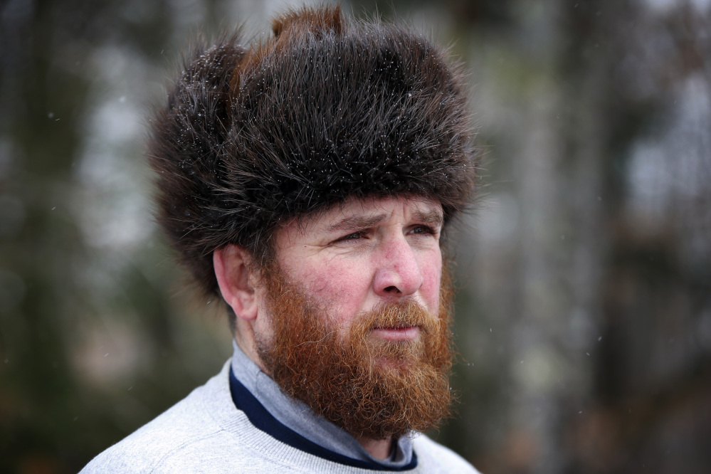 Trapper Brian Cogill wears a fur hat he had made from a beaver he trapped.