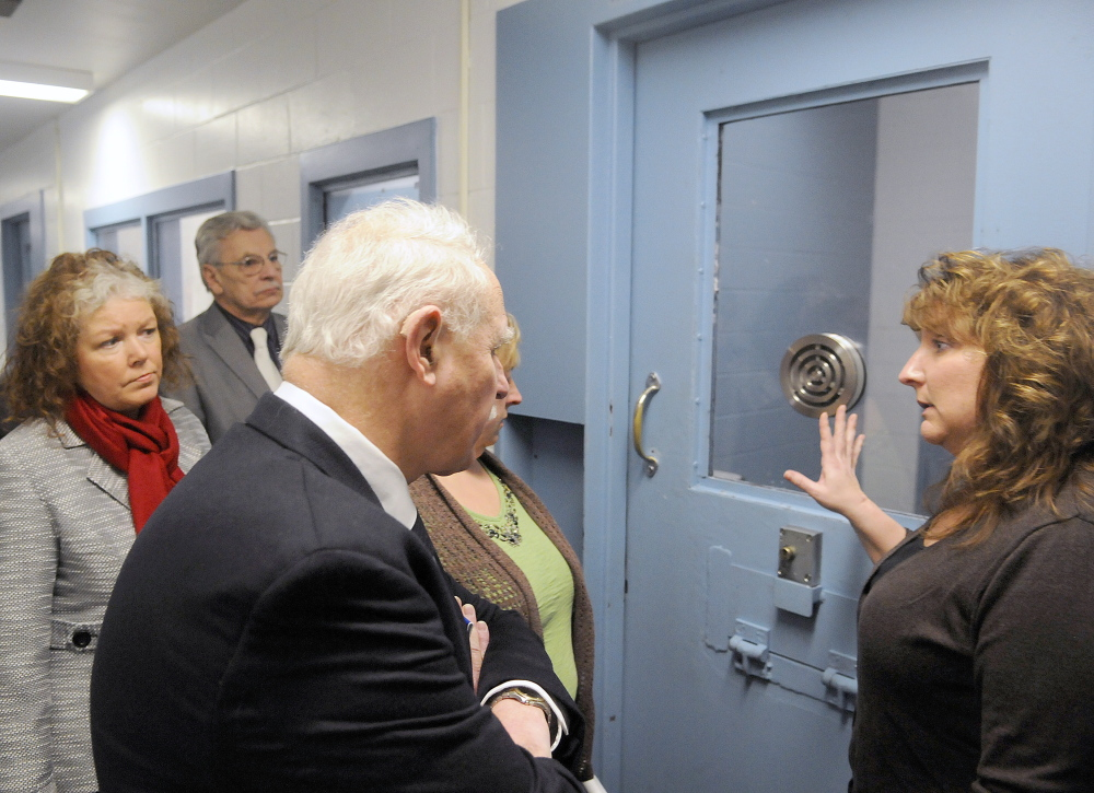 Kennebec County Corrections Capt. Marsha J. Alexander, right, shows members of the Legislature's Criminal Justice and Public Safety Committee the exterior of a cell that holds high-risk inmates, during a tour of the jail in Augusta on Wednesday.
