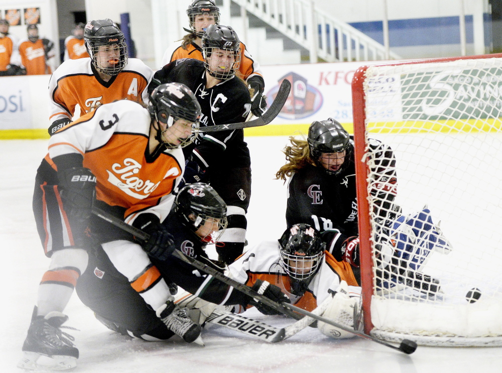 Biddeford goalie Rebekah Guay scrambles to control the puck, but is beaten to it by Kathryn Clark, lower left, who scores late in the third period for Cape Elizabeth/Waynflete/South Portland in a 3-2 win Wednesday night at Biddeford.