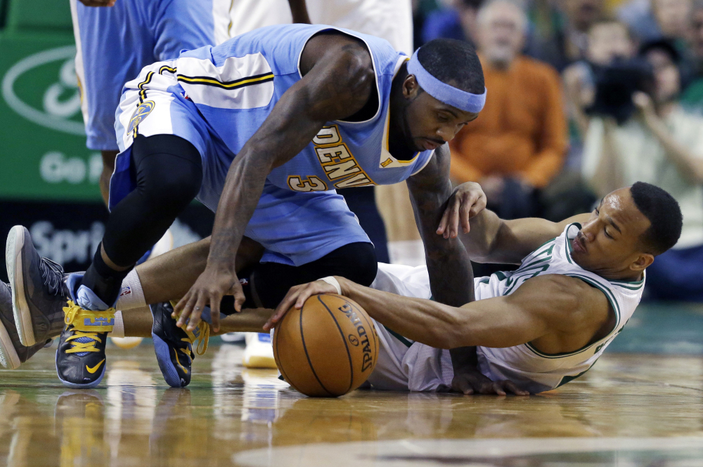 Celtics guard Avery Bradley gains control of the ball during a scramble with Denver Nuggets guard Ty Lawson in the second half of Wednesday night's game in Boston. The Celtics won, 104-100.