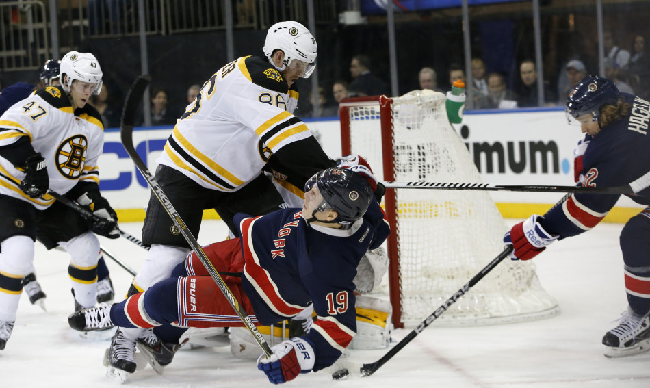 Bruins defenseman Kevan Miller levels New York Rangers right wing Jesper Fast as Rangers left wing Carl Hagelin maneuvers the puck in the crease in the second period of Wednesday night's game at Madison Square Garden in New York.