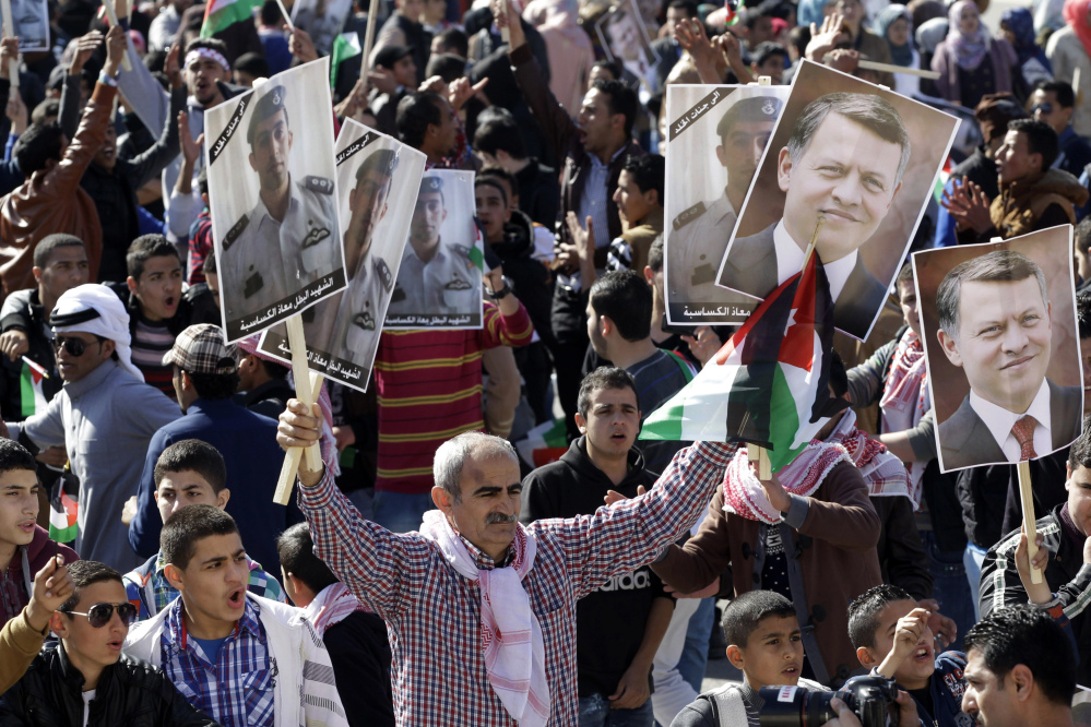 Jordanians show their support for the government's strikes against the Islamic State during a rally Thursday in Amman. Two posters of Jordan's King Abdullah II are held at right and the others show the murdered Jordanian pilot Lt. Muath al-Kaseasbeh.