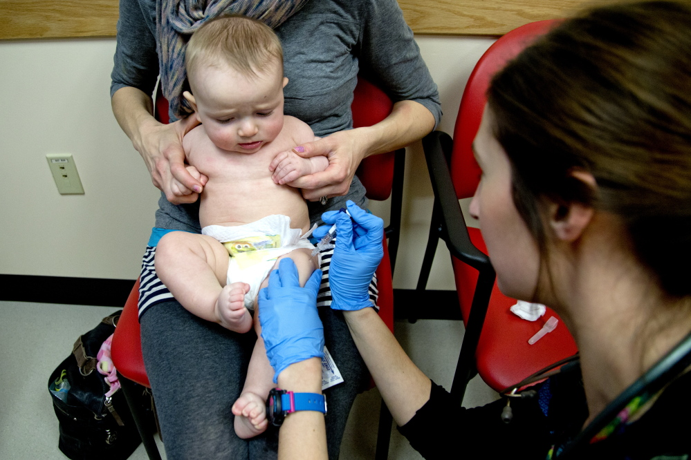 """Bethany Hickey holds Alexander as he is vaccinated by clinical assistant Laura Boyer at Intermed Pediatric Care. Hickey worries about giving her children too many shots all at once, but nevertheless believes in the value of vaccinations. """"If enough people go without vaccinations, it's a health risk to the general population,"""" she said."""