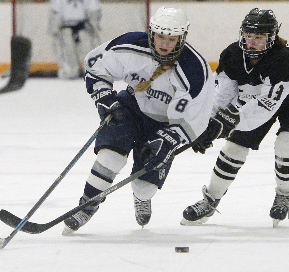 Jenny Holmquist, left, of Yarmouth/Freeport/Gray-New Gloucester, skates forward with Jessica Boulet of Saint Dominic in a girls' hockey quarterfinal game played Feb. 5. Yarmouth/Freeport/Gray-New Gloucester won the game, 8-1.
