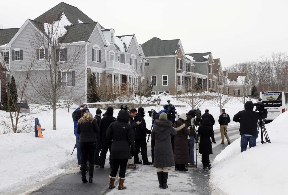 Media members and police officers stand near a bus sitting in front of the North Attleborough, Mass., home of former New England Patriots football player Aaron Hernandez, rear, during a site visit by the jury in his murder trial Friday.
