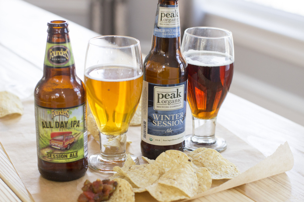 After losing ground to smaller craft brewers – such as those whose products are pictured above, Founders All Day IPA of Michigan and Portland's own Peak Organic Winter Session Ale – Anheuser-Busch, the country's biggest brewery, is wooing its own core consumers, the folks who likely wouldn't reach for a craft beer in any case.