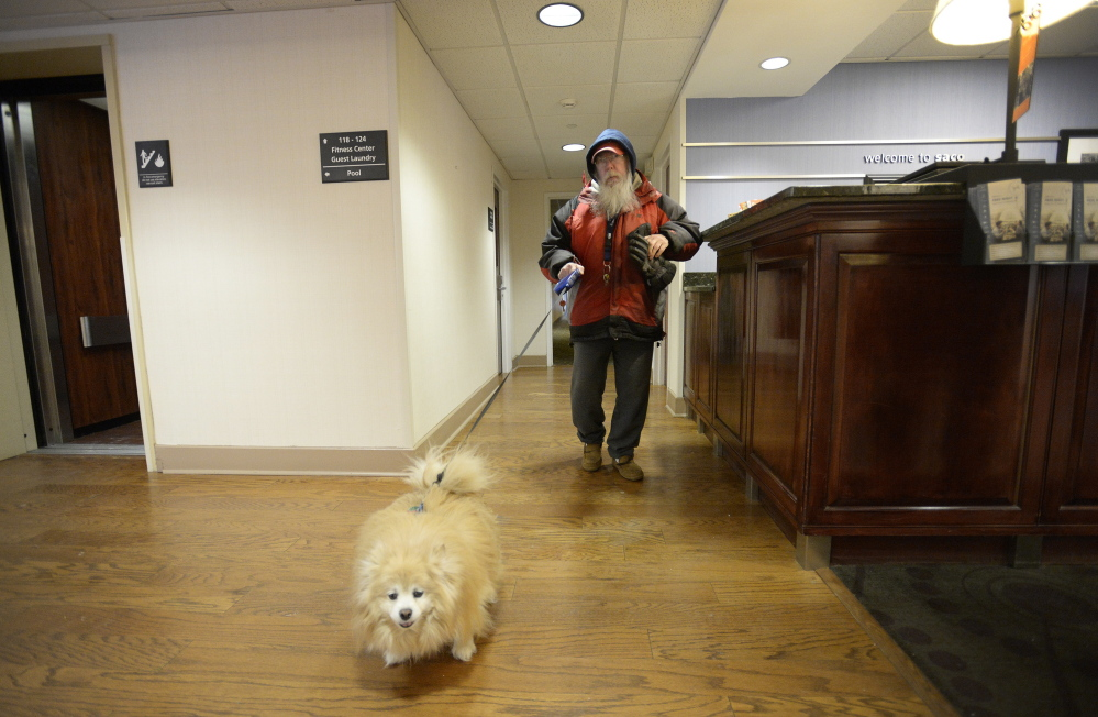 Richard Sweeney, who was displaced by the Jan. 29 fire at Centennial Place in Old Orchard Beach, walks through the lobby at the Hampton Inn in Saco with Easy Boy on Thursday. Some tenants worry that new short-term housing won't accept pets.