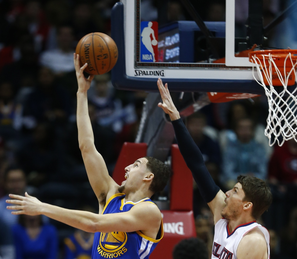 Golden State Warriors guard Klay Thompson goes up for a shot as Atlanta Hawks guard Kyle Korver defends during the Hawks' 124-116 win Friday in Atlanta.