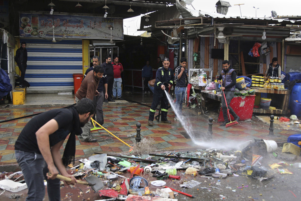 Baghdad municipality workers help clean up the site of a suicide bombing that targeted a street filled with hardware stores, killing over 20 people and wounding at least 45, in the Iraqi capital's southeastern neighborhood of New Baghdad, on Saturday.