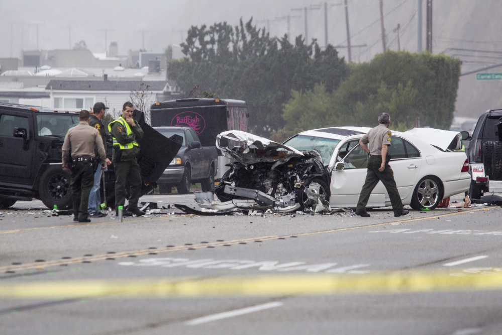 Los Angeles County Sheriff's deputies investigate the scene of a collision involving three vehicles in Malibu, Calif., on Saturday.