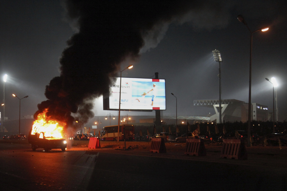 A pickup truck bursts into flames as a riot breaks out outside of a soccer match between Egyptian Premier League clubs Zamalek and ENPPI at Air Defense Stadium in a suburb east of Cairo, Egypt. The riot broke out Sunday night outside of the major soccer game, with a stampede and fighting between police and fans killing at least 22 people, authorities said.