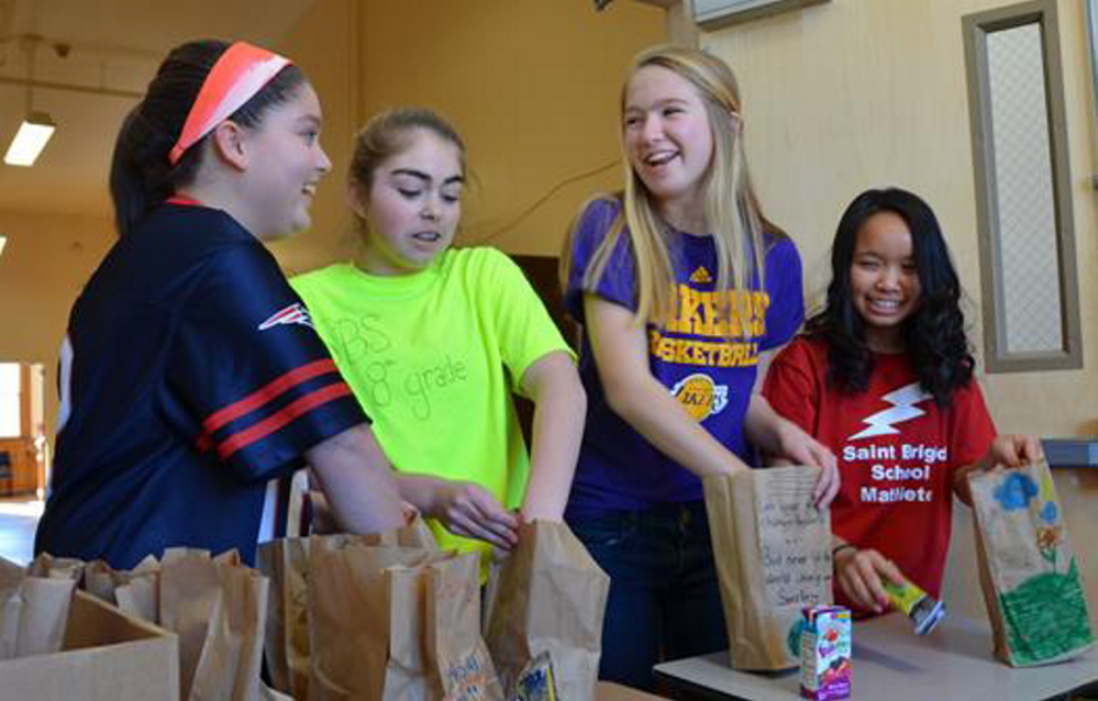 Students at St. Brigid Catholic School in Portland prepare bags of healthy snacks collected by eighth-graders to distribute to children in community programs.