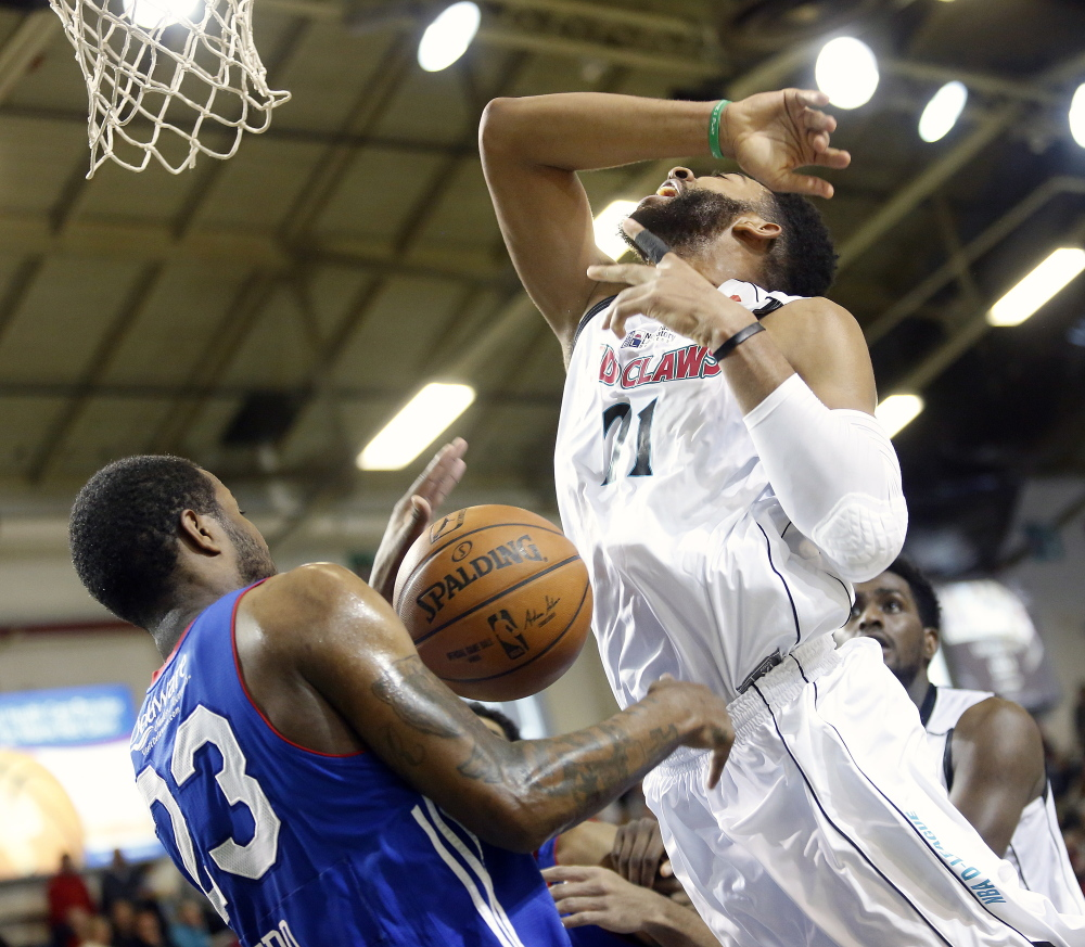 Christian Watford of the Red Claws is fouled by Victor Rudd of the 87ers while driving to the basket in the second quarter Sunday at the Portland Expo.