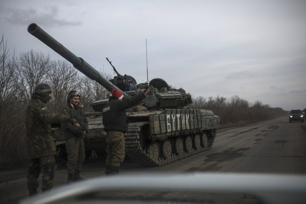 Ukrainian soldiers ask for a lift as that stand near their military vehicle near Debaltseve, eastern Ukraine, Sunday.