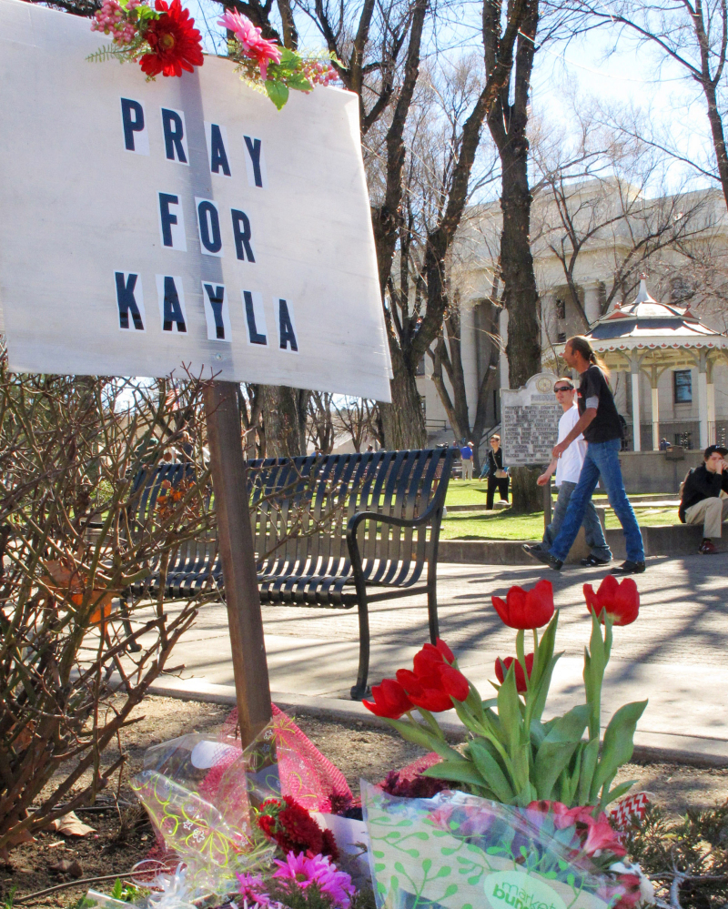 A memorial, at left, honoring American hostage Kayla Mueller, above, is growing at a corner of the courthouse plaza in Prescott, Ariz. Mueller was helping refugees in war-torn Syria when she was captured in August 2013.