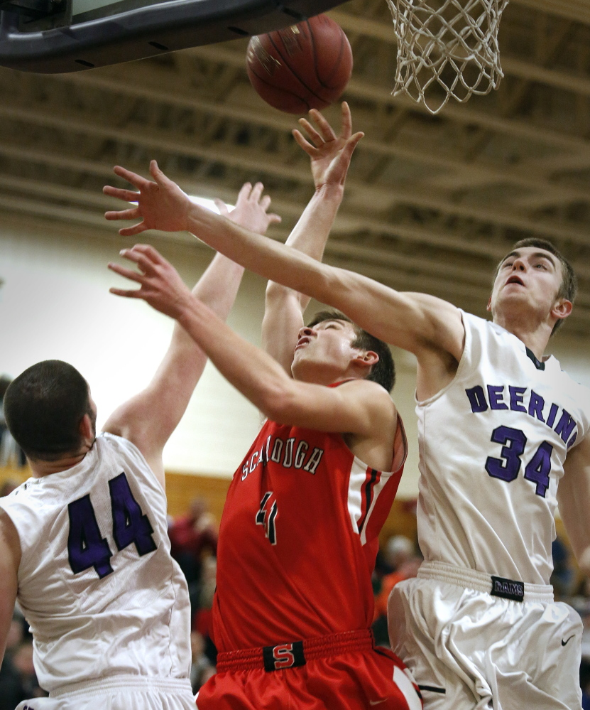 Raffaele Salamone, left, and Jacob Coon of Deering combine to block a shot by Reece Langerquist during the first quarter of their playoff game.  Derek Davis/Staff Photographer
