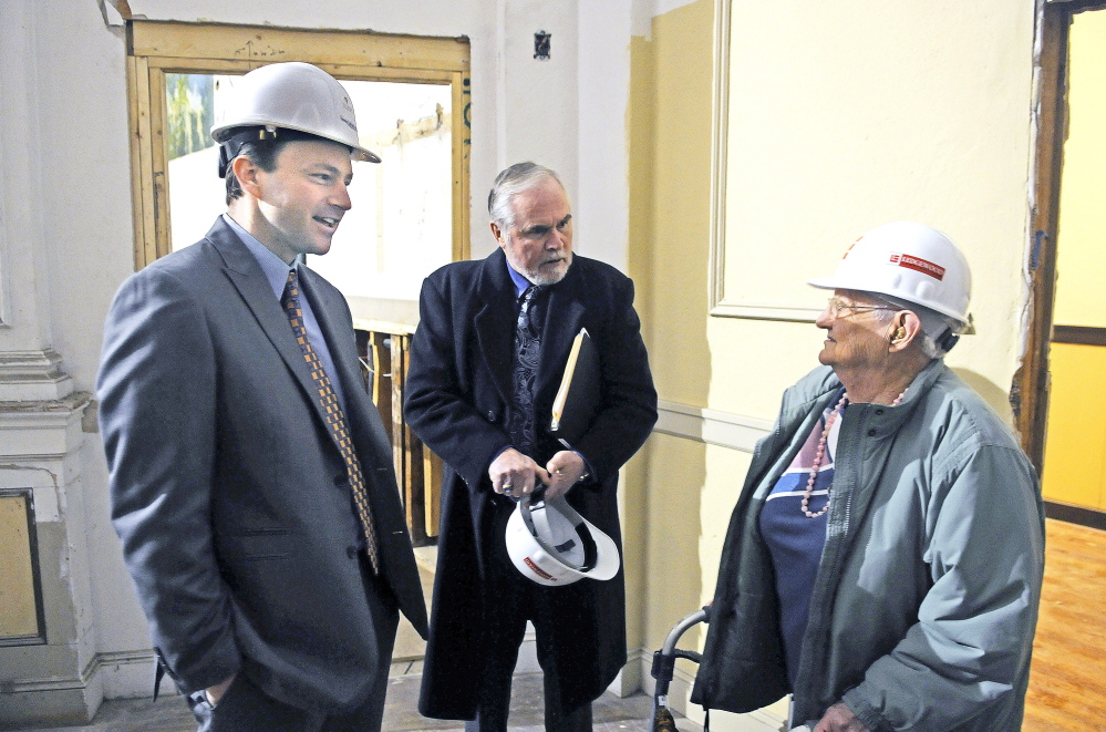 Dorothy Mead, 91, talks Wednesday with Speaker of the House Mark Eves, D-North Berwick, left, and state Sen. David Burns, R-Whiting, at the flatiron building that once served as Cony High School in Augusta. The building is being renovated into senior housing.