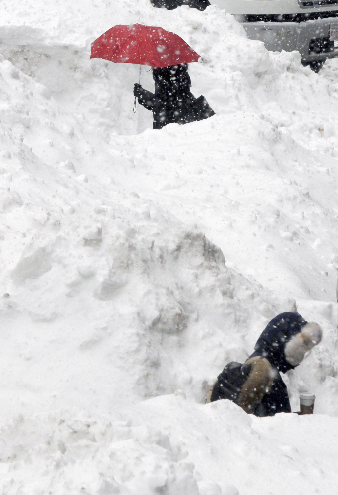 Commuters walk between piles of snow on a street in downtown Boston on Wednesday.