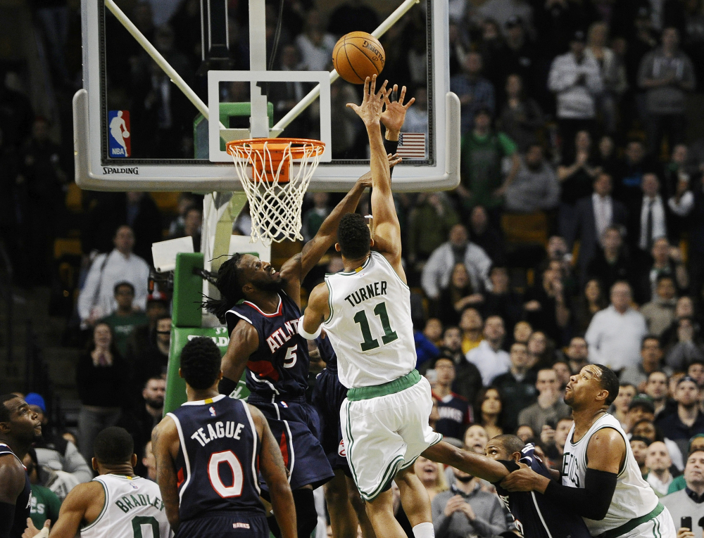 The Celtics' Evan Turner shoots the game-winning basket over the Atlanta Hawks' DeMarre Carroll (5) with 0.2 seconds left in Wednesday night's game in Boston. The Celtics won, 89-88, on Turner's buzzer-beater.