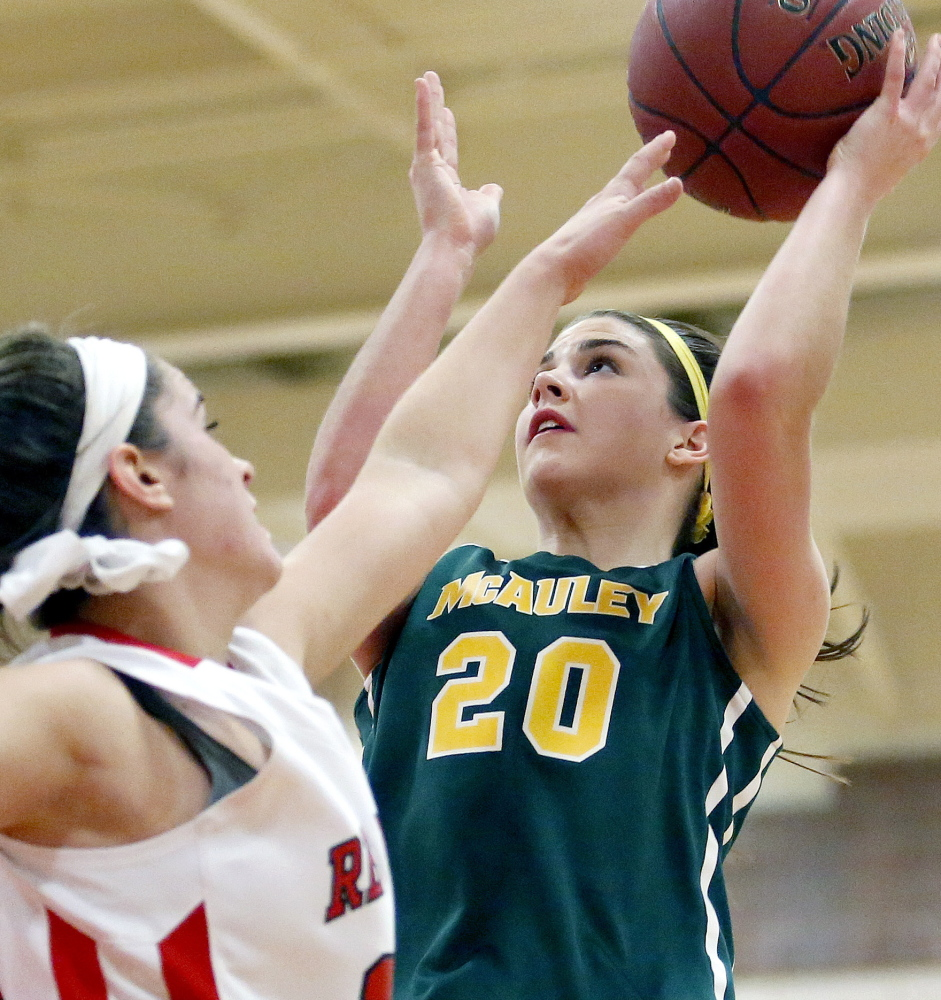 McAuley's Olivia Dalphonse gets off a shot over South Portland's Lydia Henderson during their game on Jan. 9. The Lions have won 17 games in a row and are four-time defending state champs, but will face stiff tourney competition.